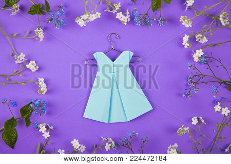 Blue Paper Origami Dress On Hanger Surrounded With Blue And White Little Flowers On Violet Backgroun