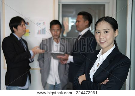 Asian Businesswoman Smiling At Camera While Colleagues Have Meeting At Office. Businessman Working W