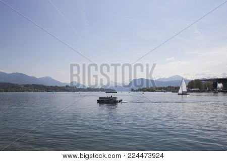 Ship in front of snow covered Alps mountains peaks on Lake Lucerne, central Switzerland. The boat sails along the lake