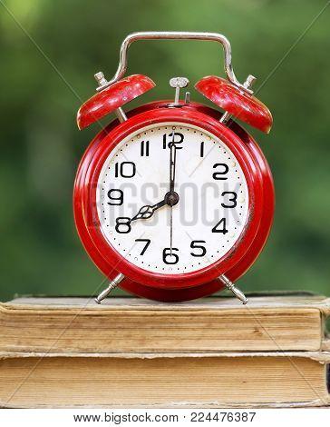 Retro red alarm clock standing on old books
