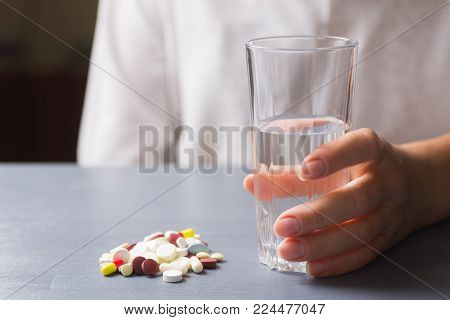 Hand Holding Glass Of Water Near Colorful Different Capsules And Pills On Table