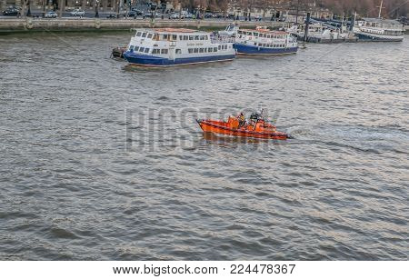 Central London, United Kingdom - December 29, 2016: Lifeboat crusing on the River Thames near Waterloo Bridge.