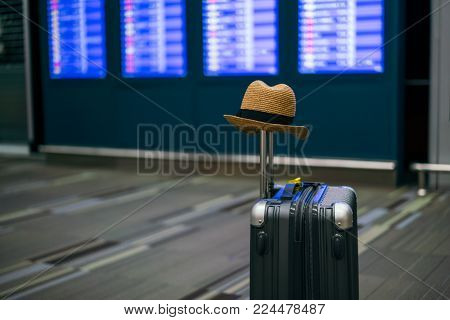 Suitcases with hipster hat in airport departure lounge, Boarding times in background, summer vacation concept, traveler suitcases in airport terminal waiting area.