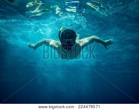 Underwater view of a young diver man swimming under blue sea under the surface with snorkelling mask for summer vacation at Similan islands, Andaman sea, Phang Nga near Phuket nad Krabi in Thailand.