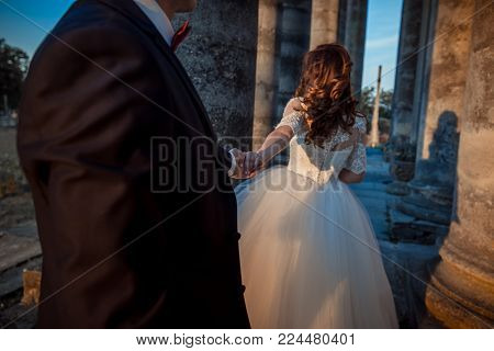 The bride with beautiful ginger curly hair is leading the groom by the hand among old columns
