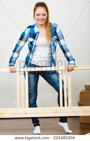 Woman assembling wooden furniture. DIY enthusiast. Young girl doing home improvement.