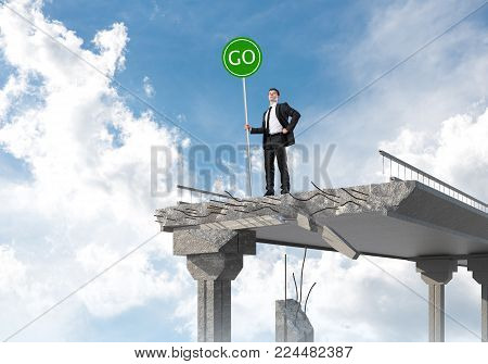 Confident businessman in suit holding green go sign while standing on broken bridge with skyscape on background. 3D rendering. poster