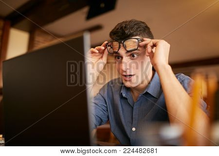 Office, business, technology, finances and internet concept. Surprised freelancer hipster man looks to laptop screen and can not believe he won lottery prize or green card visa. Pop-eyed successfull amazed businessman trader raises one's glasses above his
