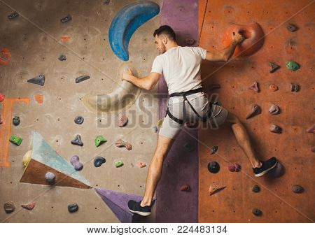 Young happy man practicing rock-climbing on artificial wall indoors. Active lifestyle and bouldering climbing, reaching the top concept