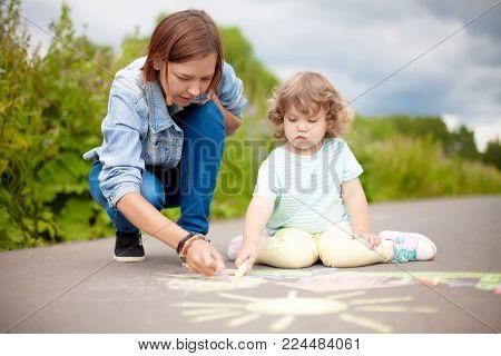 Babysitter Or Kindergarten Concept. Children Drawing With Color Chalk.