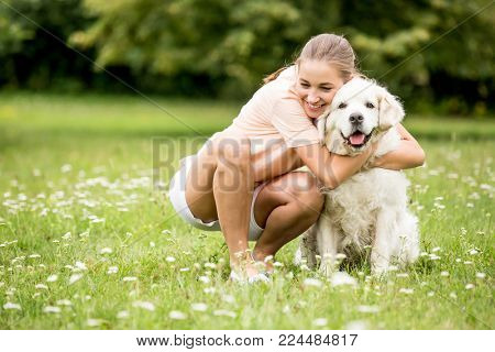 Woman hugs dog with love at garden in summer as friendship concept
