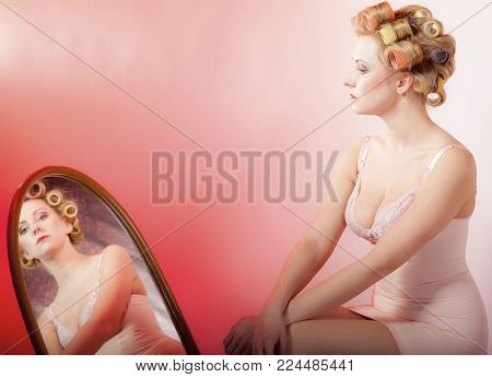 Sexy thoughtful woman preparing to party, girl in underwear with curlers in hair looking at the mirror pink background poster