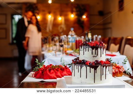 Two level white wedding cake, decorated with fresh red fruits and berries, drenched in chocolate. Bright banquet table decoration on background of couple, lights and guests gifts.