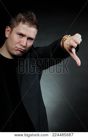 disappointed young man showing thumb down hand sign looking with negative expression disapproval on black background