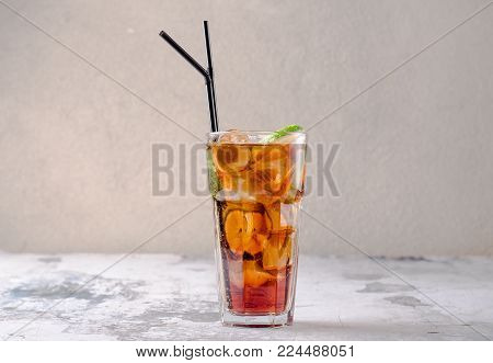 Rum and cola Cuba Libre drink with lime and ice on on a gray background, selective focus. Fruit drink with ice. Food and drink concept, text place