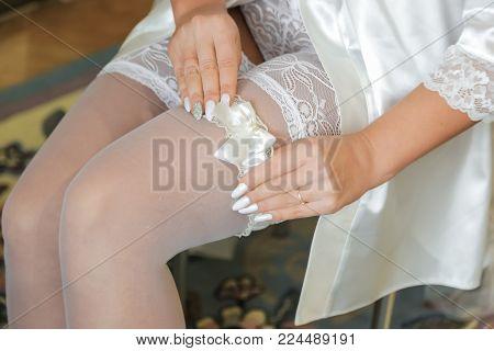 Bride wearing wedding garter. A woman demonstrates her sexy legs.