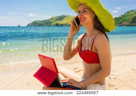Fashionable young woman talking on mobile phone while using a tablet on the beach in a sunny day of summer in Flores Island, Indonesia