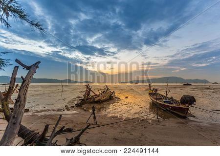 Fishing boat at the beach (long-tail boats) and boat carcass in low water and the beautiful sunrise at Phuket Island, Thailand.