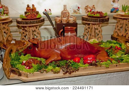 A young whole, baked pig, lying on a festive table decorated with herbs. Cossack table. Wedding snack