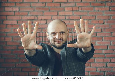 Young smiling man with hands in air to say stop or hypnotist gesture, selective focus