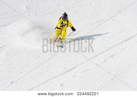 A male skier freerider with a beard descends the backcountry at high speed from the slope leaving a trail of snow powder behind him. The concept of freeriding culture and backcountry destinations in extreme skiing