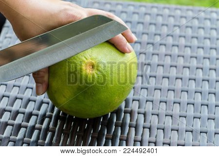 Pomelo on brown plastic rattan weave table. Close up. Pomelo on brown plastic rattan weave table. Close up. Hands are peeling grapefruit.