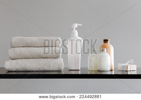 Towels with shampoo, conditioner, shower milk and handmade soap on neutral background.