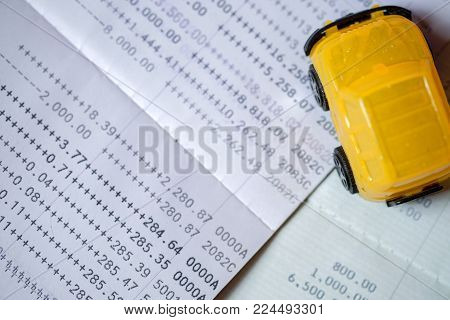 Yellow toy car placed on a bank passbook on top-view, with concept to pay in installments. In order to buy car, Payments are made in installments, the buyer must pay interest under the terms of bank.