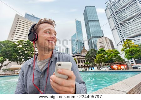 Young business man in city center of Hong Kong, China listening to smart phone with headset outside during summer. Asian travel lifestyle.
