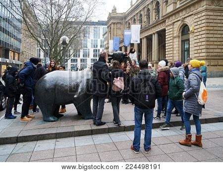 Frankfurt, Germany - January 27, 2018: International tourist crowd gathering around the bull and bear sculpture in front of historic Frankfurt Stock Exchange building to take photos.