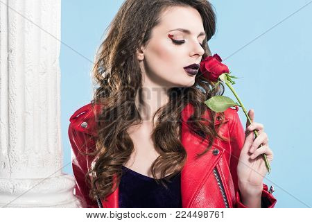 attractive girl sniffing red rose isolated on blue, valentines day concept