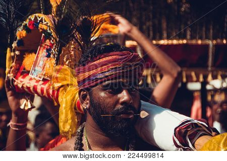 BATU CAVES, SELANGOR, MALAYSIA - 31 JANUARY 2018 Hindu devotees celebrate Thaipusam festival with procession and offerings. Man portrait. Religion concept. Culture and traditions. Pierced tongue