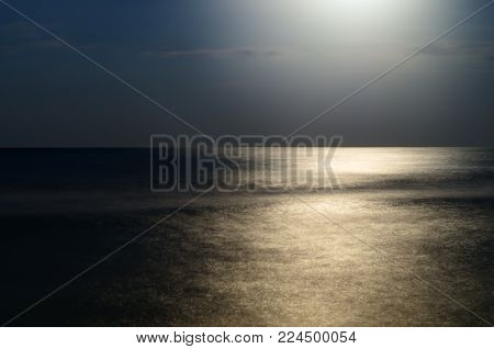 moonlight at night over the sea, reflection. horizon blue sky with clouds. a picture on a long time. Beautiful landscape.