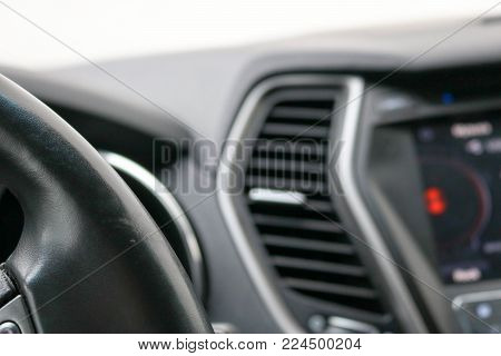 The angle of the leather black steering wheel in the car on the background of the dashboard.