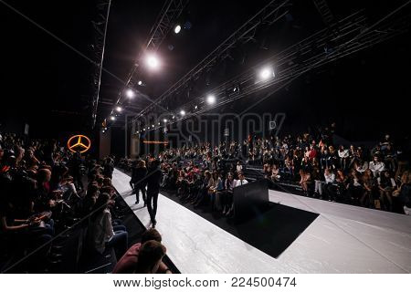 MOSCOW, RUSSIA - OCT 24, 2017: People in auditorium and models on catwalk in Manege during day four of Mercedes Benz Fashion Week Russia spring-summer season 2018.
