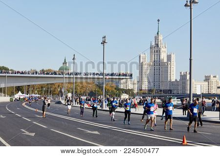 MOSCOW, RUSSIA - SEP 24, 2017: Runners participants of Promsvyazbank Moscow marathon at Moskvoretskaya embankment of Moskva River and spectators on Floating bridge.