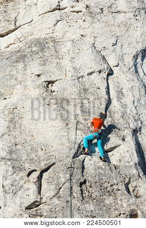 Poland, Podlesice - March 04, 2017: Side View Of Adult Male Rock Climber On Vertical Flat Wall With