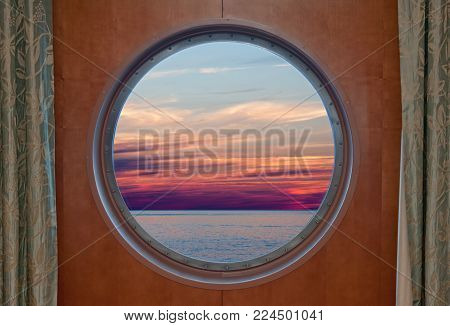 Ocean and evening sky sunset seen through the porthole of a ship
