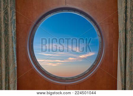 Blue sky seen through the porthole of a ship