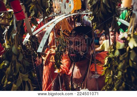 BATU CAVES, SELANGOR, MALAYSIA - 31 JANUARY 2018 Hindu devotees celebrate Thaipusam festival. People portrait. Religion concept. Culture and traditions. Asia travel. Face and body pierced man. Closeup