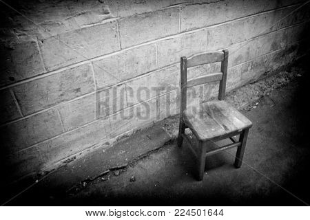Gritty and grainy black and white image of an old abandoned chair in an industrial hallway