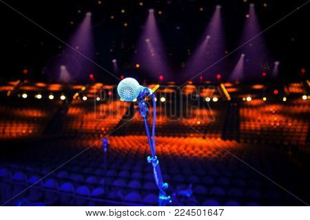 Microphone on stage overlooking a large empty concert venue - show cancellation or stage fright concept