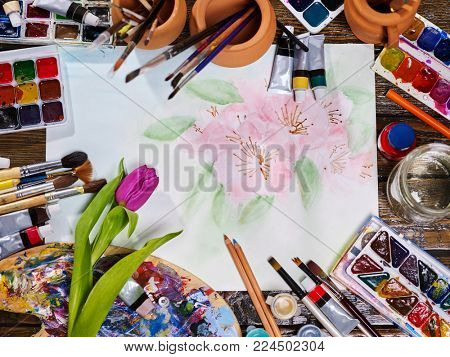 Authentic paint brushes still life in art class school. Group of brush in clay jar. Bouquet of tulip flowers as symbol of spring discounts. Copy space for text. Spring discounts on drawing course.