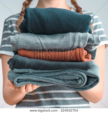 Square shot of a young woman holding a pile of clothes, isolated on white background