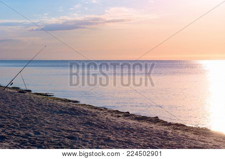 fishing rod on the beach, sunrise reflected on the watery surface, horizon calm. sea shore. Toning