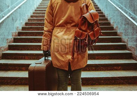 woman climb stairs with bags at railway station travel concept