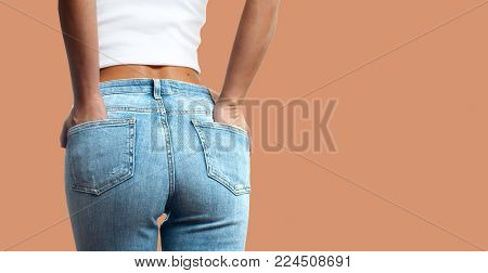 Woman wearing of jean pants from back. Female bottom in tight jeans on pastel background