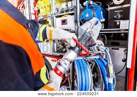 Fire fighter wearing helmet and uniform checking hydraulic cutter at fire engine