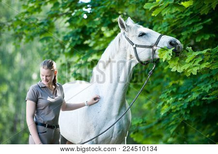 Pretty Young Blondy Cheerful Teenage Girl Equestrian Standing With Her Favorite White Horse Eating G