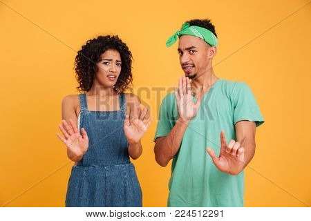 Portrait of a disgusted young african couple dressed in summer clothes gesturing with hands isolated over yellow background